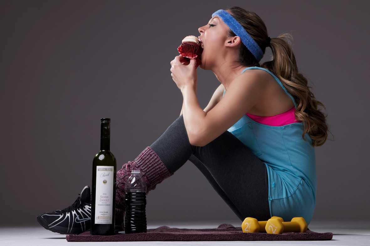 На фото фитоняшка с гантелями и бутылкой вина.